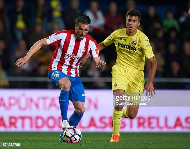 Rodrigo Hernandez of Villarreal competes for the ball with Xavi Torres of Real Sporting de Gijon during the La Liga match between Villarreal CF and...