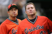 Rodrigo Lopez and Karim Garcia of the Baltimore Orioles look on from the dugout during the game against the Minnesota Twins at Camden Yards on July...