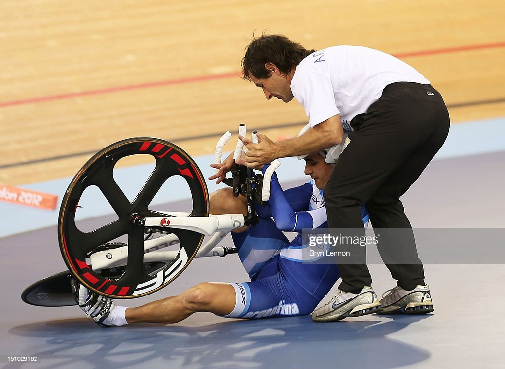 Rodrigo Lopez of Argentina receives assistance after crashing in the Men's Individual Cycling C1 Pursuit qualification on day 2 of the London 2012 Paralympic Games at Velodrome on August 31, 2012 in London, England.