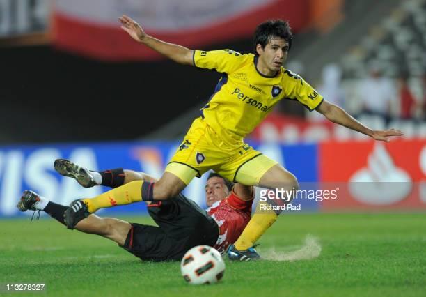 Rodrigo Lopez of Argentina's Estudiantes struggles for the ball with Ivan Piris of Paraguay's Cerro Porteño during a match as part of the 2011...