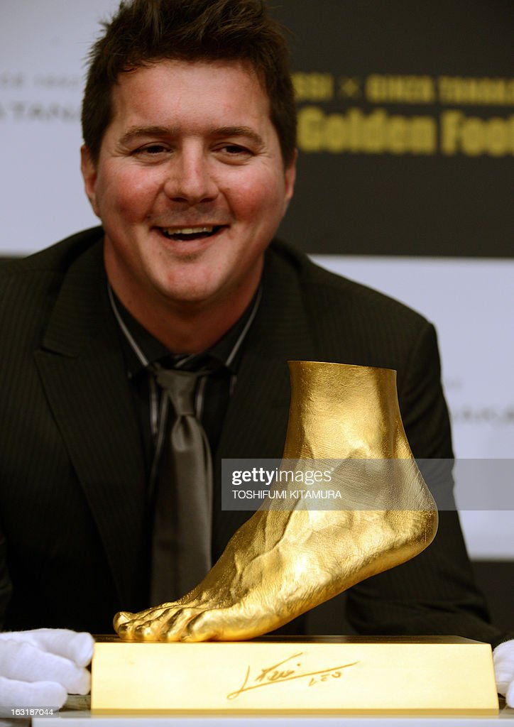 Rodrigo Messi, brother of football star Lionel Messi of Argentina, smiles from behind the golden replica of Lionel Messi's left foot during its press preview in Tokyo on March 6, 2013. Priced at about 5.25 million USD, the 25-kilogram golden foot was created by Tokyo-based jewelry retailer, Ginza Tanaka, to commemorate Messi's record-breaking Ballon d'Or for four consecutive years and the world-record 91 goals he scored a calender year. AFP PHOTO/TOSHIFUMI KITAMURA