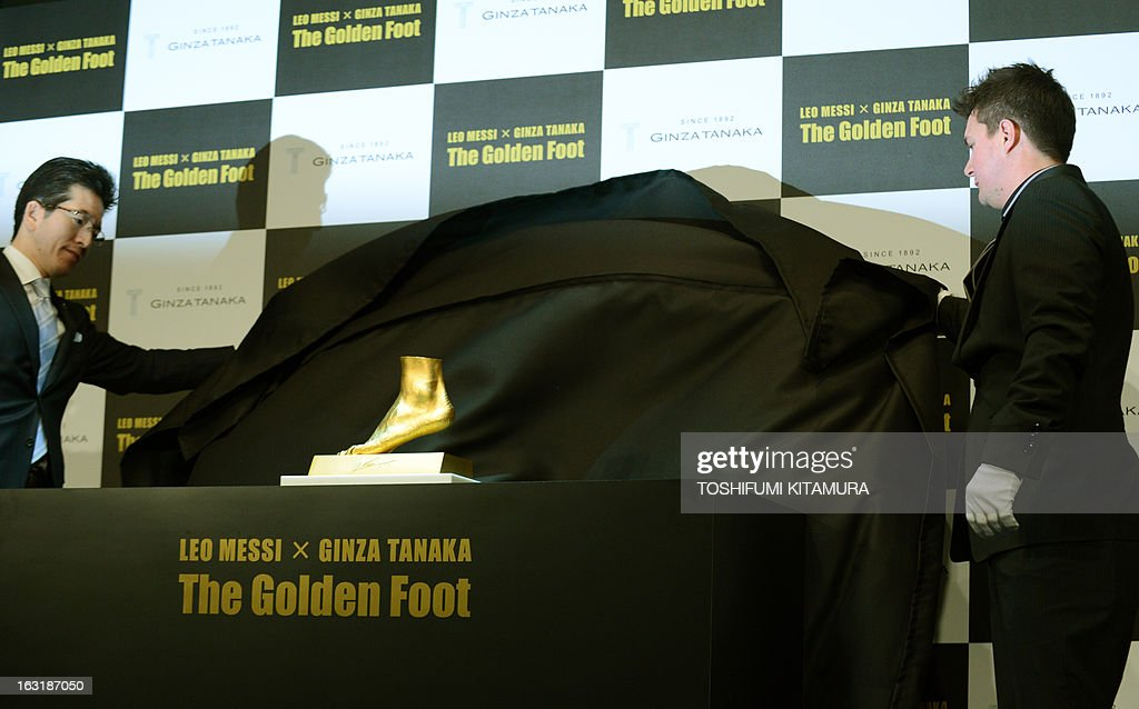 Rodrigo Messi, brother of football star Lionel Messi of Argentine (R) and Ginza Tanaka President Masakazu Tanaka (L) unveil the golden replica of Lionel Messi's left foot during its press preview in Tokyo on March 6, 2013. Priced at about 5.25 million USD, the 25-kilogram golden foot was created by Tokyo-based jewelry retailer, Ginza Tanaka, to commemorate Messi's record-breaking Ballon d'Or for four consecutive years and the world-record 91 goals he scored a calender year.