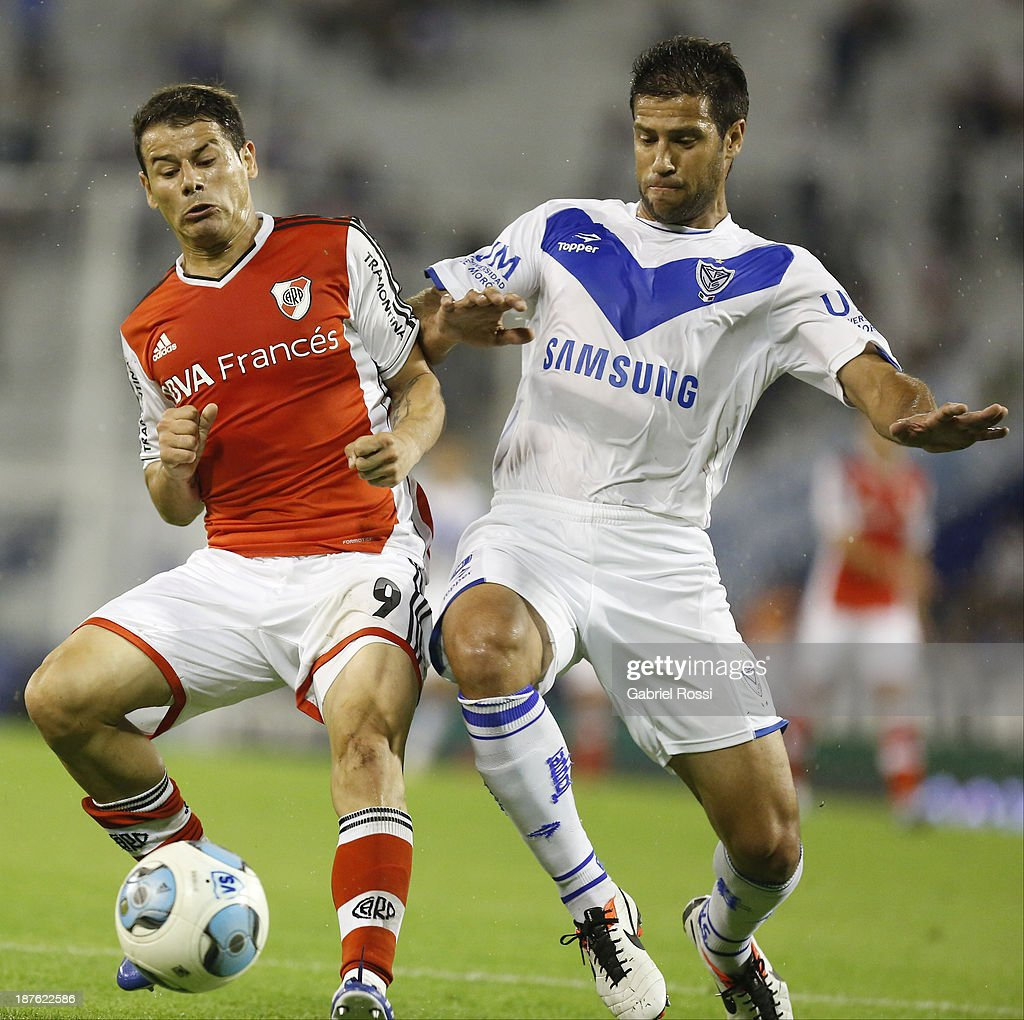 Rodrigo Mora of River Plate fights for the ball with <a gi-track='captionPersonalityLinkClicked' href=/galleries/search?phrase=Sebastian+Dominguez&family=editorial&specificpeople=2474032 ng-click='$event.stopPropagation()'>Sebastian Dominguez</a> of Velez Sarsfield during a match between Velez Sarsfield and River Plate as part of round 15th of Torneo Inicial at Jose Amalfitani Stadium on November 10, 2013 in Buenos Aires, Argentina.