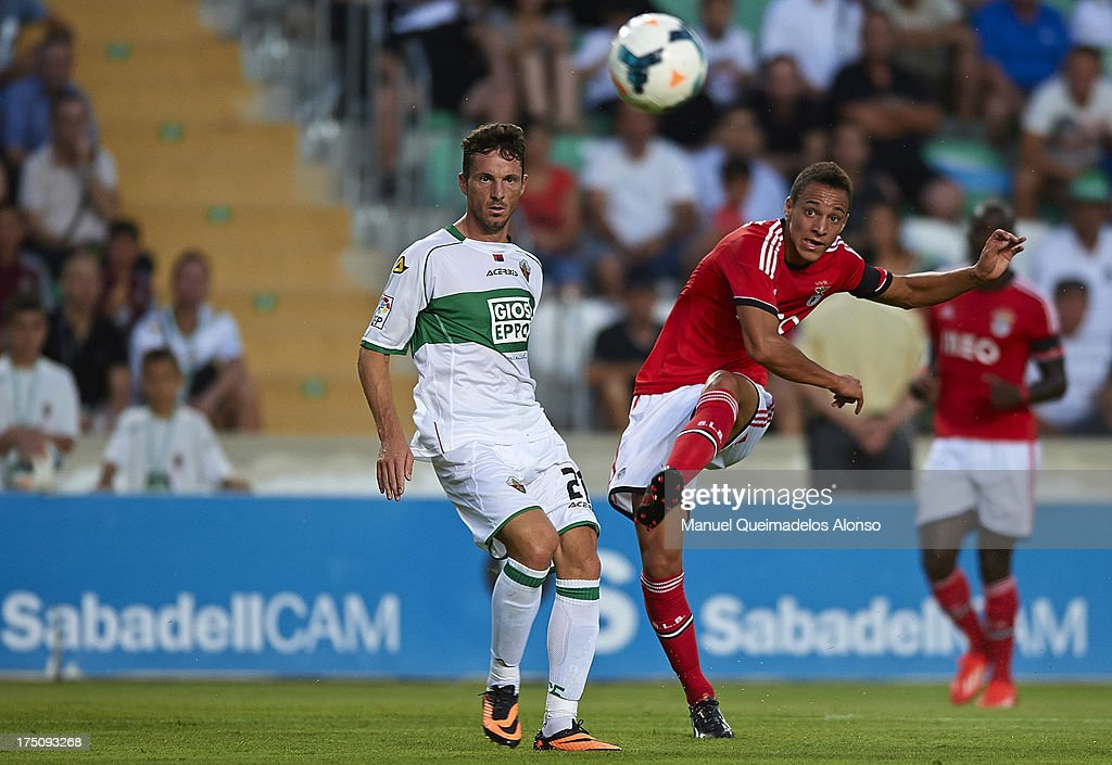 Rodrigo (R) of Benfica scores a goal in front of Albacar of Elche during a friendly match between Elche CF and Benfica at Estadio Martinez Valero on July 31, 2013 in Elche, Spain.