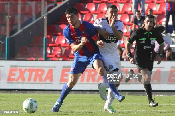 Rodrigo Rojas of Cerro Porteño fights for the ball with Julian Benitez of Olimpia during a match between Olimpia and Cerro Porteño as part of the...
