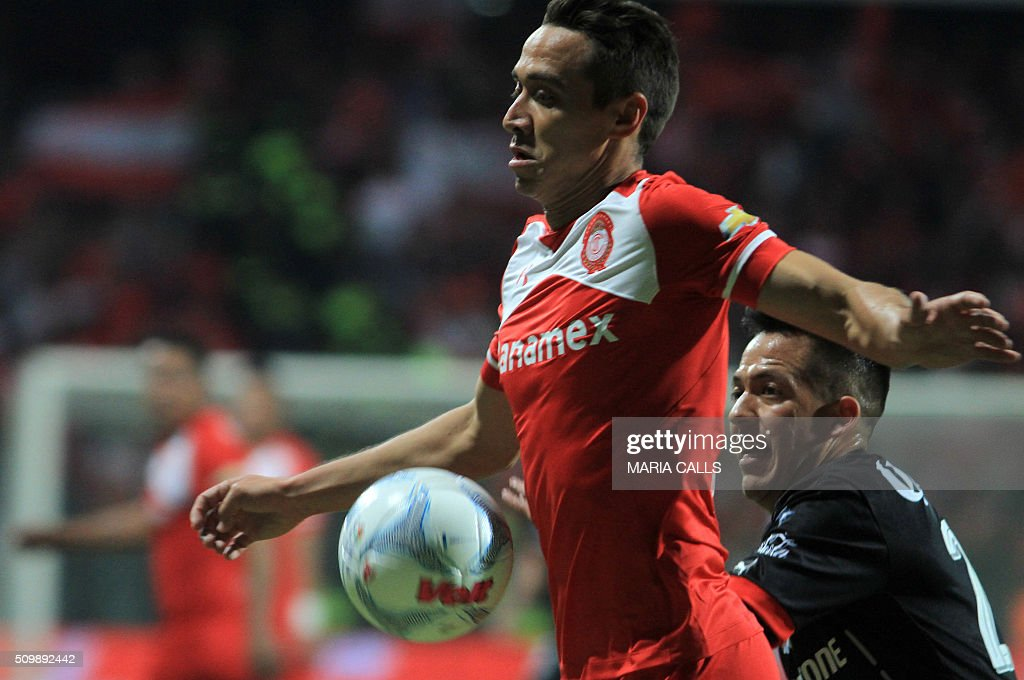 Rodrigo Salinas (R) of Atlas jumps for the ball with Carlos Esquivel of Toluca during the Mexican Clausura 2016 Tournament at the Nemesio Diez stadium on February 12, 2016, in Toluca ,Mexico. / AFP / MARIA CALLS