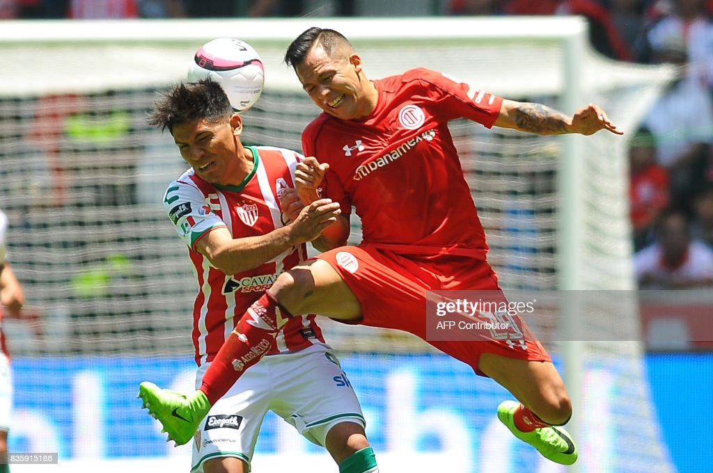 Rodrigo Salinas (R) of Toluca jumps for the ball with Martin Barragan of Necaxa during their Mexican Apertura football tournament match at the Nemesio Diez stadium in Toluca, Mexico, on August 20, 2017. /