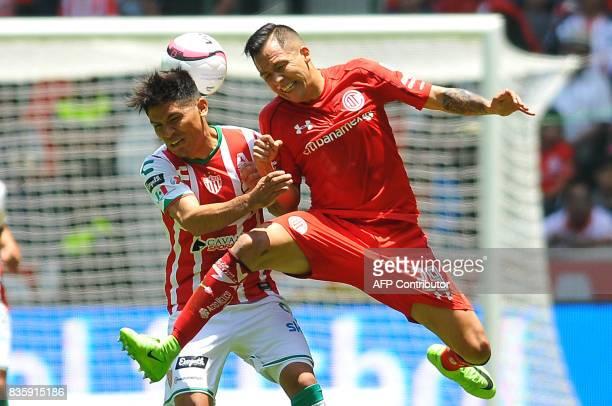 Rodrigo Salinas of Toluca jumps for the ball with Martin Barragan of Necaxa during their Mexican Apertura football tournament match at the Nemesio...