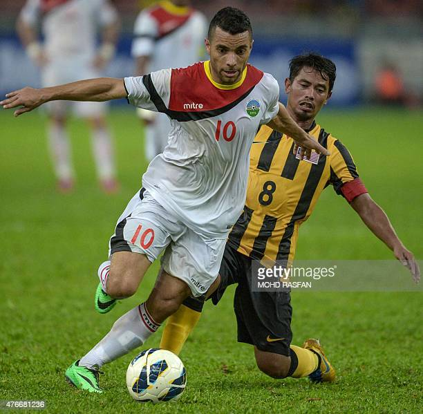 Rodrigo Sousa of Timor Leste vies for the ball with Safiq Rahim of Malaysia during their 2018 World Cup qualifying Group A match in Kuala Lumpur on...