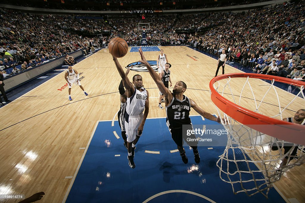 <a gi-track='captionPersonalityLinkClicked' href=/galleries/search?phrase=Rodrigue+Beaubois&family=editorial&specificpeople=5299423 ng-click='$event.stopPropagation()'>Rodrigue Beaubois</a> #3 of the Dallas Mavericks drives to the basket past <a gi-track='captionPersonalityLinkClicked' href=/galleries/search?phrase=Tim+Duncan&family=editorial&specificpeople=201467 ng-click='$event.stopPropagation()'>Tim Duncan</a> #21 of the San Antonio Spurs on December 30, 2012 at the American Airlines Center in Dallas, Texas.