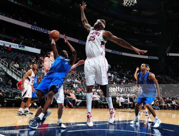 Rodrigue Beaubois of the Dallas Mavericks shoots against Kirk Hinrich and Erick Dampier of the Atlanta Hawks on April 26 2012 at Philips Arena in...