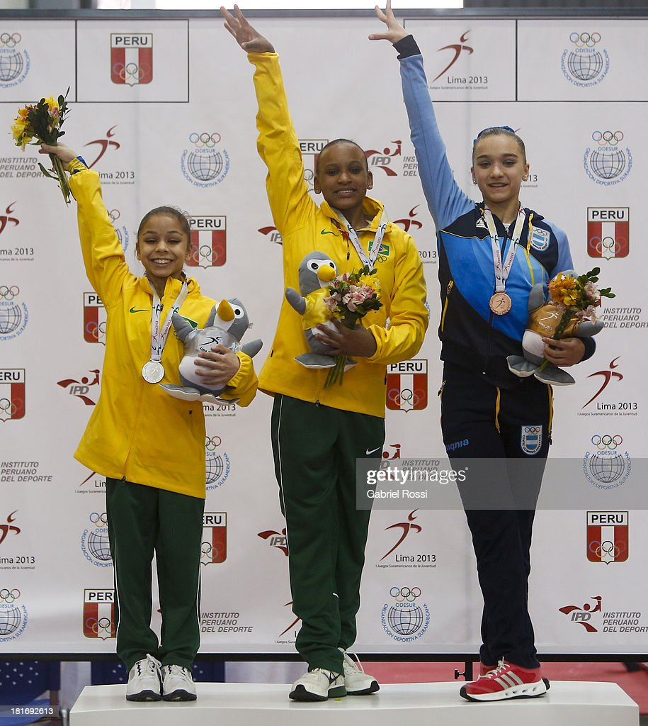 Rodriguez De Andrade of Brazil (C), Flavia Lopes Saraiva of Brazil (L) and Agustina Santamarina (R) pose for a picture in the podium of Women's Individual all-around as part of the I ODESUR South American Youth Games at Coliseo Miguel Grau on September 23, 2013 in Lima, Peru.