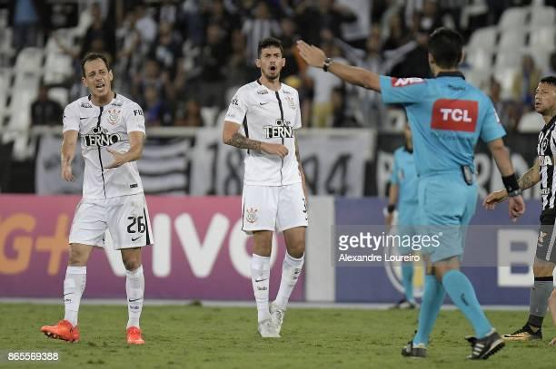 Rodriguinho and Pedro Henriqueof Corinthians recevies a yellow card from referee Rodrigo Batista Raposo during the match between Botafogo and...