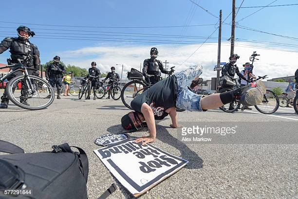 Rodstarz of Rebel Diaz busts a move in front of police during the End Poverty Now rally march downtown to RNC on July 18 2016 in Cleveland Ohio