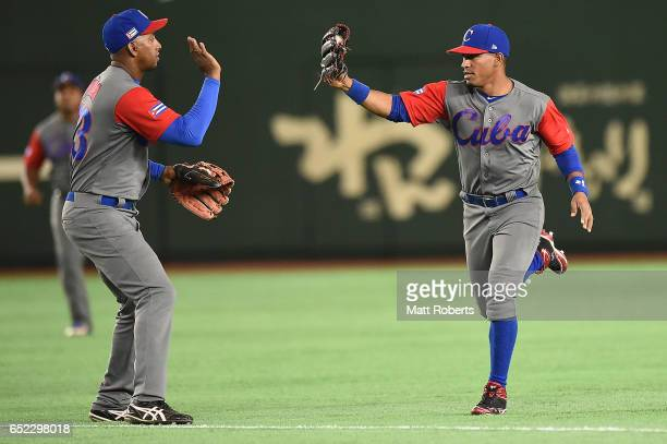 Roel Santos celebrates with Alfredo Despaigne of Cuba after catching a liner during the World Baseball Classic Pool E Game One between Cuba and...