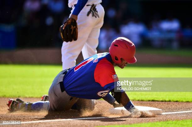 Roel Santos of Alazanes de Granma from Cuba slides safe into third base in a match against Tigres de Licey from Dominican Republic at the Tomateros...