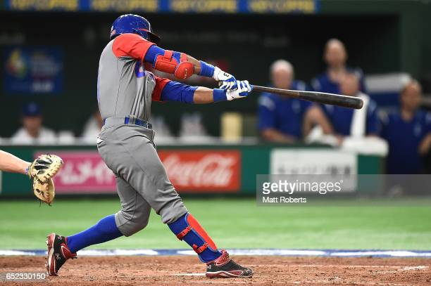 Roel Santos of Cuba hits a single grounder to right field in the fifth inning during the World Baseball Classic Pool E Game One between Cuba and...
