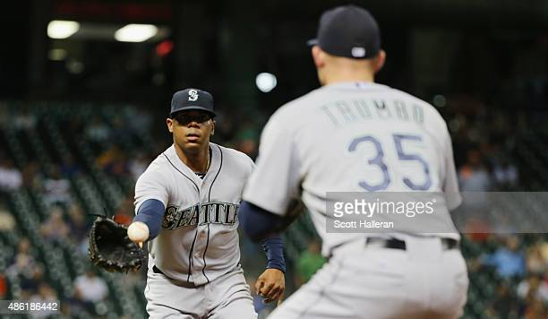 Roenis Elias of the Seattle Mariners tosses the baseball to Mark Trumbo to end the third inning of their game against the Houston Astros at Minute...