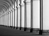 Row of column in colonnade. Perspective view of long arc vault corridor. Black and white image.