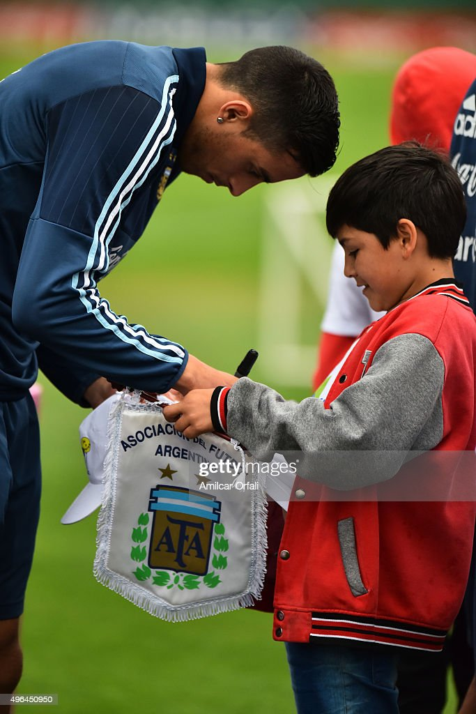 <a gi-track='captionPersonalityLinkClicked' href=/galleries/search?phrase=Rogelio+Funes+Mori&family=editorial&specificpeople=6717732 ng-click='$event.stopPropagation()'>Rogelio Funes Mori</a> of Argentina gives an autograph to a kid fan during a training session at Argentine Football Association (AFA) 'Julio Humberto Grondona' training camp on November 09, 2015 in Ezeiza, Argentina. Argentina will face Brazil on November 12, 2015.