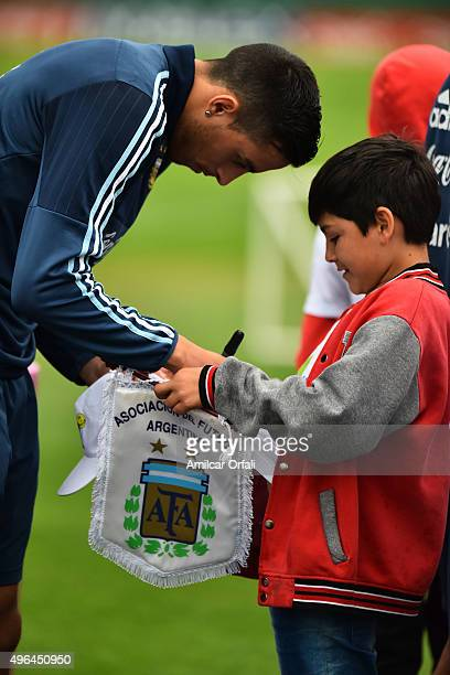 Rogelio Funes Mori of Argentina gives an autograph to a kid fan during a training session at Argentine Football Association 'Julio Humberto Grondona'...