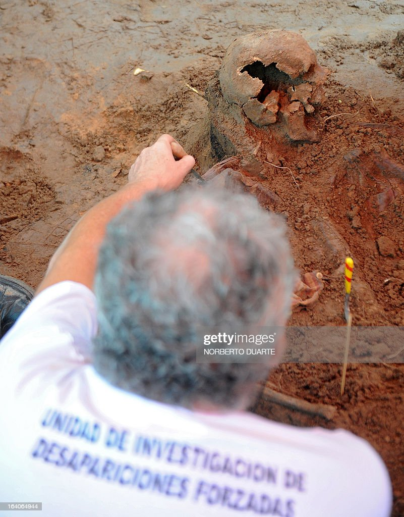 Rogelio Goiburu, whose father went missing in 1978, observes a human skull in the dirt on the premises of the Specialized Police Group headquarters in the outskirts of Asuncion on March 19, 2013. The human remains are believed to have been buried in the 1970´s, during the dictatorship of Alfredo Stroessner (1954-1989), in which hundreds went missing. AFP PHOTO/Norberto Duarte
