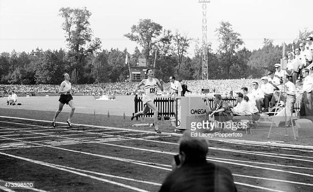 Roger Bannister of Great Britain crosses the finish line to win the 1500 metres race during the European Championships at the Berne Neufeld Stadium...