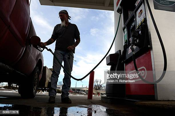 Roger Beatch fills his truck up with gas at a gas station on January 25 2016 in Kersey Colorado With oil prices now tumbling into the $20 range per...