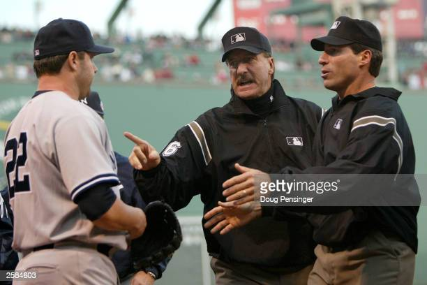 Roger Clemens of the New York Yankees is instructed to remain in the dugout by umpire Tim McClelland after Karim Garcia collided with Todd Walker as...