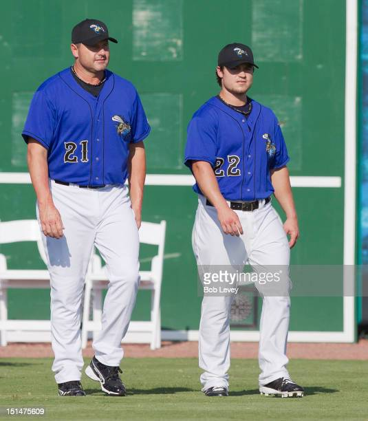 Roger Clemens of the Sugar Land Skeeters and his son Koby Clemens walk back to the clubhouse after having a team photograph taken before playing the...