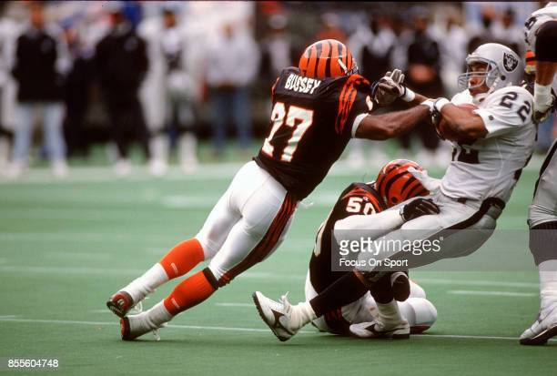 Roger Craig of the Los Angeles Raiders gets tackled by Barney Bussey and James Francis of the Cincinnati Bengals during NFL football game November 24...