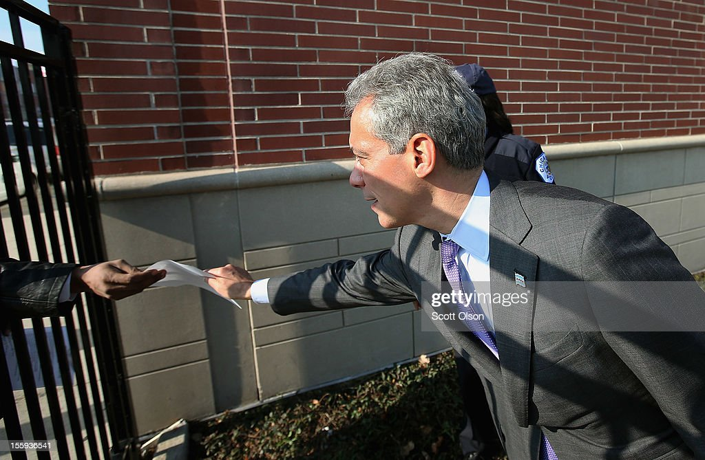 Roger Dickson passes his resume through a fence to Chicago Mayor Rahm Emanuel (R) as he prepares to get in line at Kennedy-King College for a job fair hosted by the city of Chicago on November 9, 2012 in Chicago, Illinois. Thousands of people waited in line beginning at 3AM for the job fair which did not open the doors until 9AM. When the doors opened the line was approximately a half-mile long.