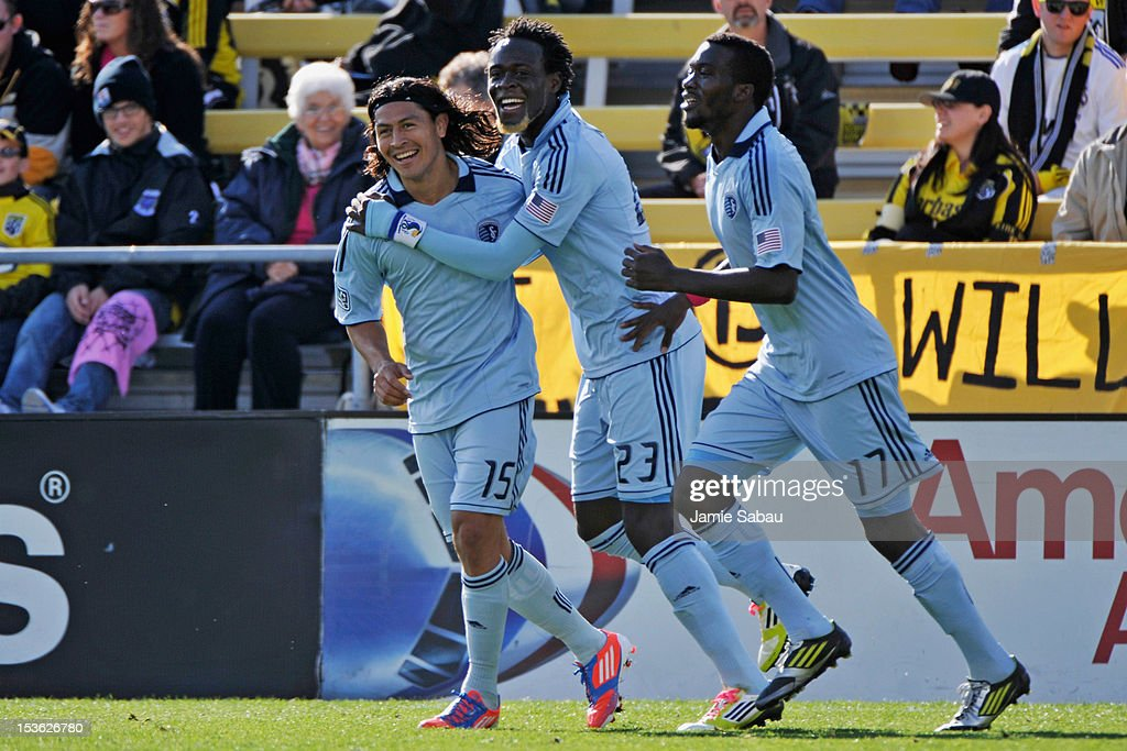<a gi-track='captionPersonalityLinkClicked' href=/galleries/search?phrase=Roger+Espinoza&family=editorial&specificpeople=4824201 ng-click='$event.stopPropagation()'>Roger Espinoza</a> #15 of Sporting Kansas City and <a gi-track='captionPersonalityLinkClicked' href=/galleries/search?phrase=Kei+Kamara&family=editorial&specificpeople=4405555 ng-click='$event.stopPropagation()'>Kei Kamara</a> #23 of Sporting Kansas City celebrate with <a gi-track='captionPersonalityLinkClicked' href=/galleries/search?phrase=C.J.+Sapong&family=editorial&specificpeople=7433612 ng-click='$event.stopPropagation()'>C.J. Sapong</a> #17 of Sporting Kansas City after Sapong's first half goal against the Columbus Crew on October 7, 2012 at Crew Stadium in Columbus, Ohio.