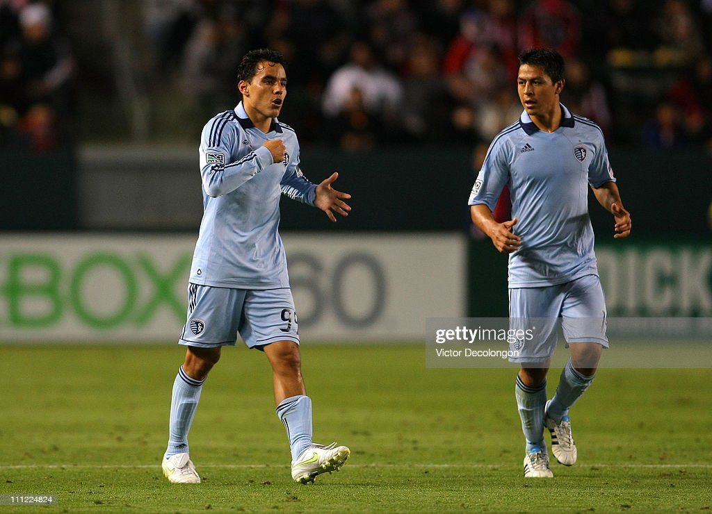 <a gi-track='captionPersonalityLinkClicked' href=/galleries/search?phrase=Roger+Espinoza&family=editorial&specificpeople=4824201 ng-click='$event.stopPropagation()'>Roger Espinoza</a> #15 of Sporting Kansas City looks on as teammate <a gi-track='captionPersonalityLinkClicked' href=/galleries/search?phrase=Omar+Bravo&family=editorial&specificpeople=490964 ng-click='$event.stopPropagation()'>Omar Bravo</a> #99 gestures to himself during the MLS match against Chivas USA at The Home Depot Center on March 19, 2011 in Carson, California. SKC defeated Chivas USA