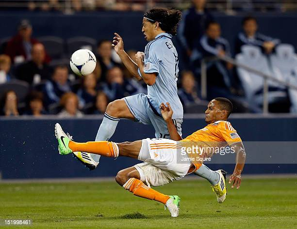 Roger Espinoza of Sporting KC controls the ball as Ricardo Clark of the Houston Dynamo slide tackles during the MLS game at Livestrong Sporting Park...