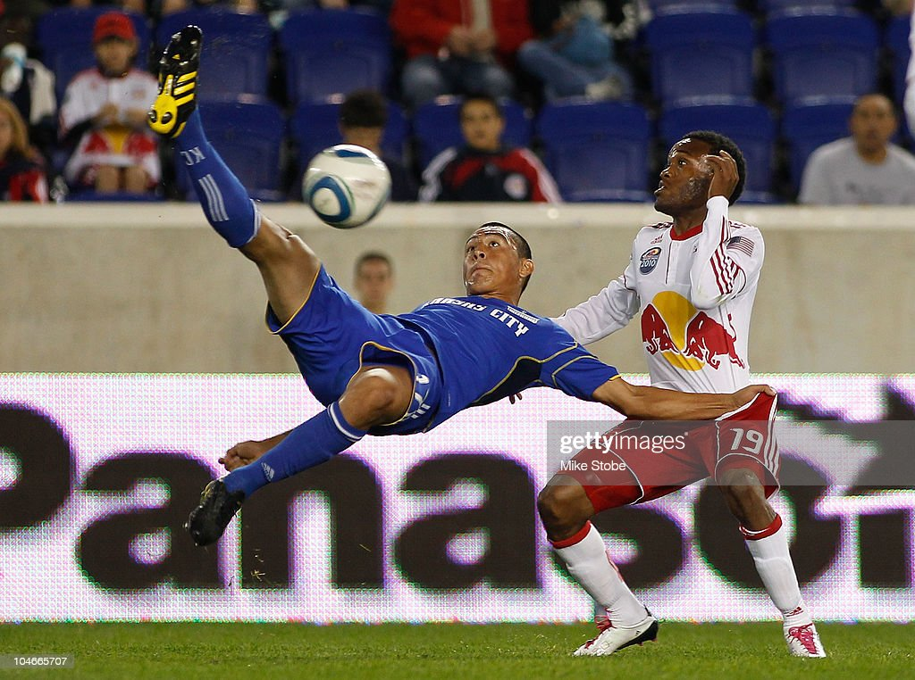 Roger Espinoza #17 of the Kansas City Wizards challenges Dane Richards #19 of the New York Red Bulls for the ball on October 2, 2010 at Red Bull Arena in Harrison, New Jersey.