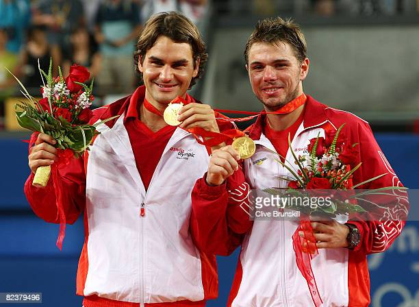 Roger Federer and Stanislas Wawrinka of Switzerland receive their gold medals after defeating Thomas Johansson and Simon Aspelin of Sweden during the...