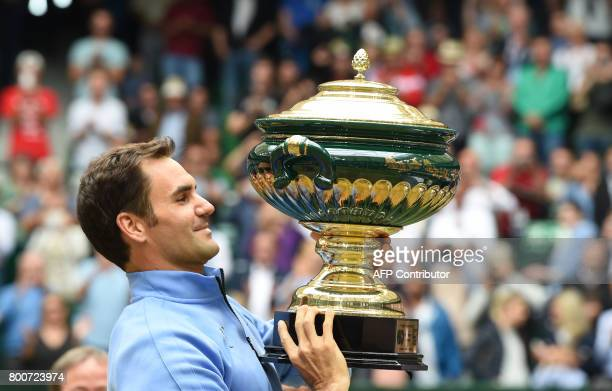 TOPSHOT Roger Federer from Switzerland poses with his trophy after winning his final match against Alexander Zverev from Germany at the Gerry Weber...