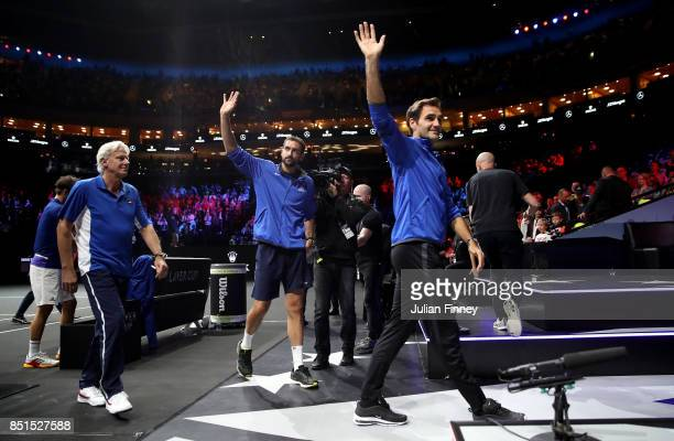 Roger Federer Marin Cilic and Bjorn Borg Captain of Team Europe waves to the crowd after watching the singles match between Dominic Thiem of Team...