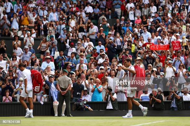 Roger Federer of Switzerland and Alexandr Dolgopolov of Ukraine walk off court after their Gentlemen's Singles first round match on day two of the...