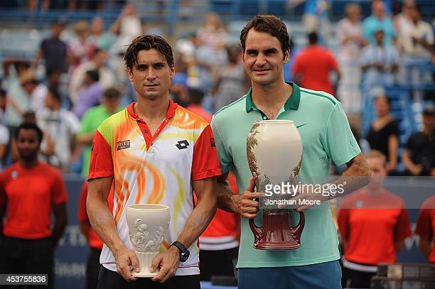 Roger Federer of Switzerland and David Ferrer of Spain pose with the winner's trophies after a final match on day 9 of the Western Southern Open at...