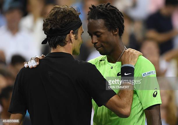 Roger Federer of Switzerland and Gael Monfils of France meet at the net after their US Open 2014 men's singles quarterfinals match at the USTA Billie...