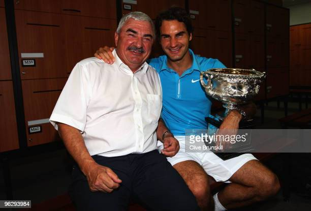 Roger Federer of Switzerland and his father Robert Federer pose with the Norman Brookes Challenge Cup in the players locker room after winning the...