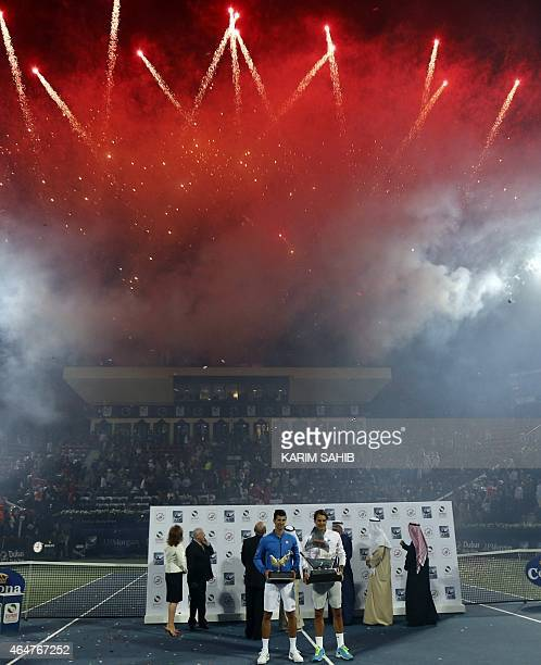 Roger Federer of Switzerland and Novak Djokovic of Serbia pose with their first and second place trophies respectively as fireworks light up the sky...