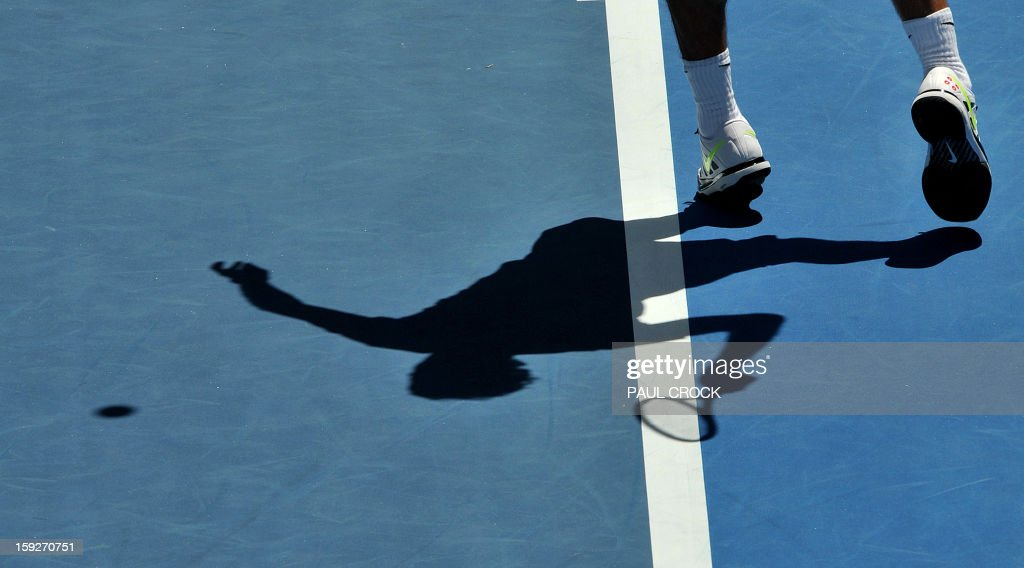 Roger Federer of Switzerland casts a shadow as he serves during a practice session for the upcoming Australian Open tennis tournament in Melbourne on January 11, 2013. The first Grand Slam tennis tournament of the year is set to run from January 14 to 27. AFP PHOTO / Paul CROCK USE