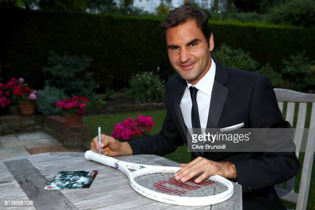 Roger Federer of Switzerland celebrates his Wimbledon record with an exclusive commemorative '8' Wilson tennis racket after his victory against Marin...