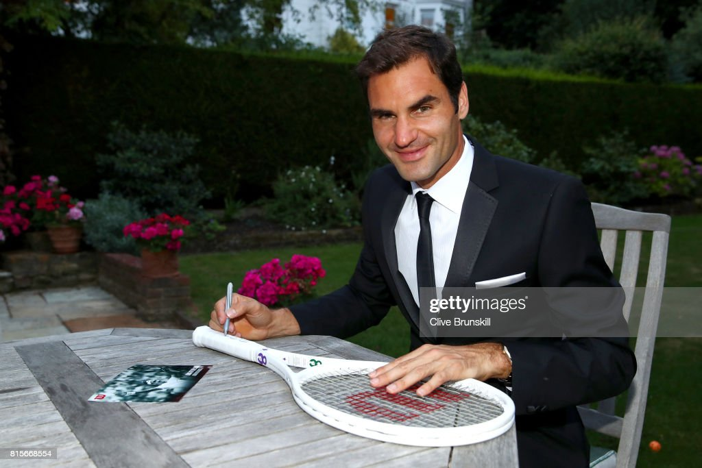 Roger Federer of Switzerland celebrates his Wimbledon record with an exclusive commemorative '8' Wilson tennis racket after his victory against Marin Cilic of Croatia on day thirteen of the Wimbledon Lawn Tennis Championships at the All England Lawn Tennis and Croquet Club on July 16, 2017 in London, England.