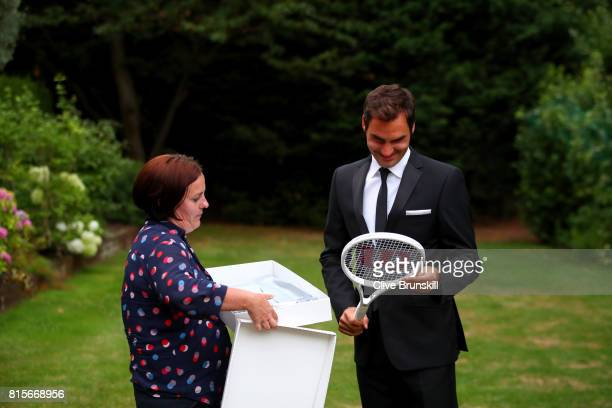 Roger Federer of Switzerland celebrates his Wimbledon record with an exclusive commemorative '8' Wilson tennis racket next to Joanne Thomas Kemp...