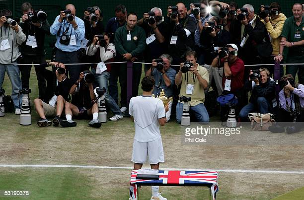 Roger Federer of Switzerland celebrates in front of the media with the trophy after winning in straight sets against Andy Roddick of the USA in the...