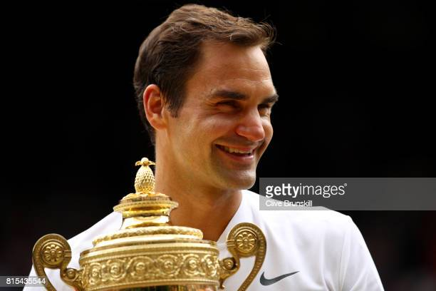 Roger Federer of Switzerland celebrates victory with the trophy after the Gentlemen's Singles final against Marin Cilic of Croatia on day thirteen of...